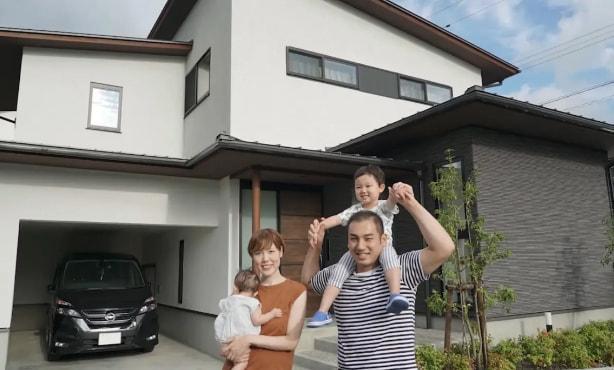 家の前でポーズを取る家族